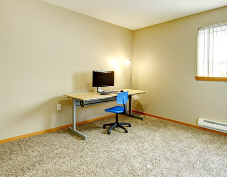 Big ivory office room with window and beige carpet floor. Furnished with small desk and computer Stock Photo - 25842177