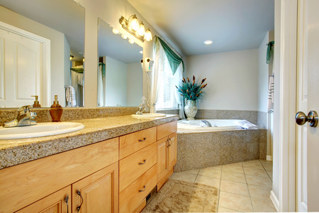antique vase: Bright beautiful bathroom with concrete floor, whirpoo and light wooden cabinets. Decorated with antique vase and dry decorative sedge Stock Photo