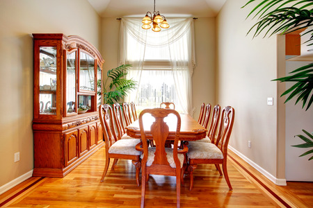 Bright dining room with high ceiling, hardwood floor, antique dining table set, wood carved storage cabinet and decorative palm tree photo