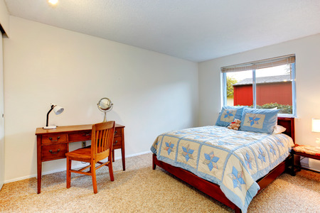 Bright bedroom for young adult with soft carpet floor and rustic desk with chair