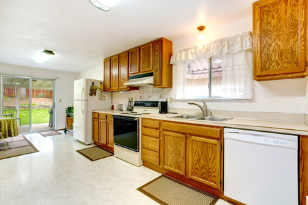 Bright kitchen with wood cabinets, tile floor, white appliances. Small dining area with walkout deck photo