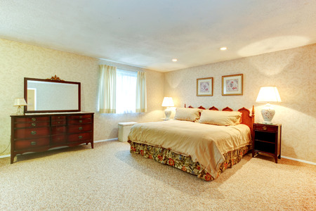 Bright bedroom with soft carpet floor, beige wallpapers. Room furnished with antique queen size bed, big cabinet with mirror and nightstand. Stock Photo - 25812834
