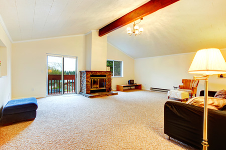 upstairs: Bright living room with vaulted ceiling and beams, carpet floor, cozy fireplace and antique furniture. Upstairs living room has a walkout deck Stock Photo