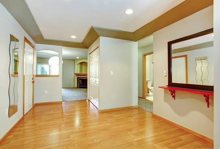 Bright hallway with hardwood floor, ivory walls and white with olive ceiling photo