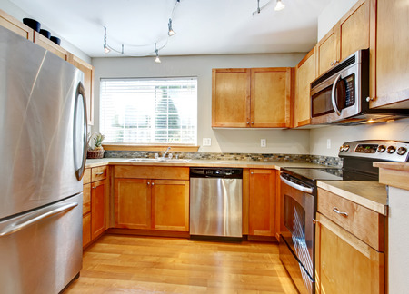 back kitchen: Bright kitchen room with wood cabinets, steel modern appliances, hardwood floor and decorated back splash