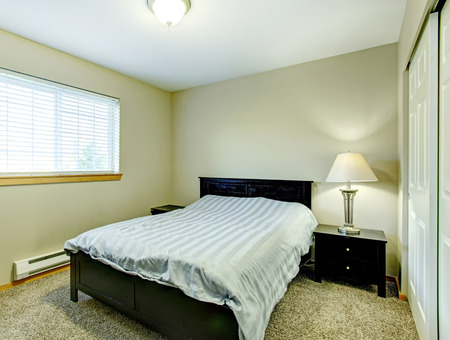 nightstands: Small cozy bedroom wtih closet, beige carpet floor, black wood bed and nightstands Stock Photo