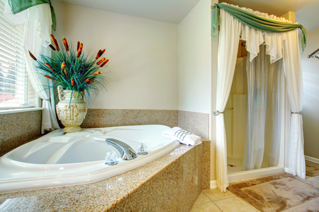 antique vase: Bright beautiful bathroom with concrete floor, open shower, whirpool. Decorated with antique vase and dry decorative sedge Stock Photo