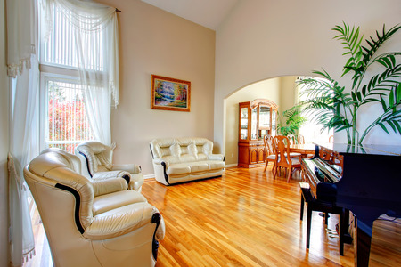 vaulted ceiling: Luxury living room with high vaulted ceiling and hardwood floor, leather couch, loveseat, piano. Stock Photo