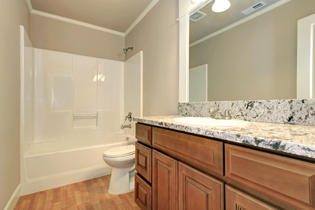 Soft colors bathroom with hardwood floor and wooden cabinets. White bath tub and toilet photo