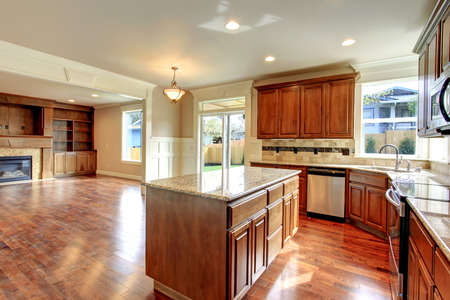 back kitchen: Beautiful kitchen with wood storage combination and tile decorated back splash. Kitchen has a walkout deck and open to living room Stock Photo