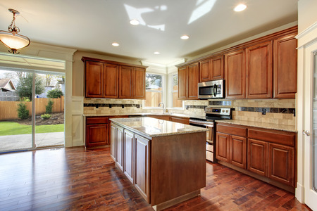 Beautiful kitchen with wood storage combination and tile decorated back splash. Kitchen has a walkout deck photo