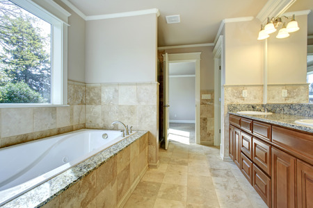 bath tub: Beige and white bathroom with tile floor, window and wooden storage combination