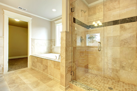 bathroom interior: Beight and white bathroom with white tub, beige tile floor, glass door shower