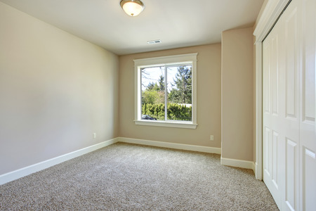 room: Bright empty room with one window, beige carpet floor, ivory walls and walk-in closet