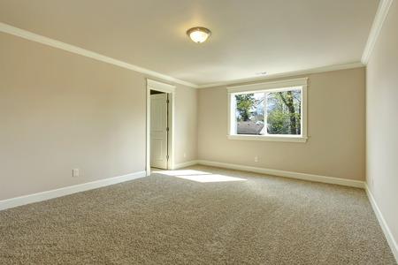 Bright empty room with one window, beige carpet floor and ivory walls Foto de archivo