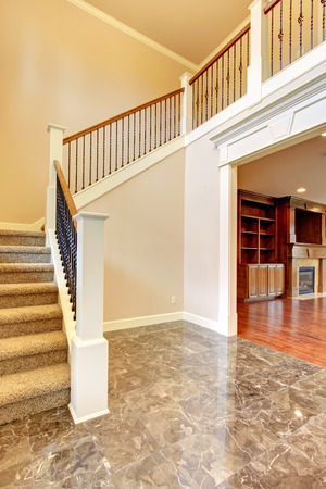 Bright Hallway With Concrete Floor And Carpet Stairs. Open To Living Room  Stock Photo
