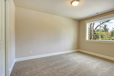 carpet: Bright empty room with one window, beige carpet floor and ivory walls Stock Photo