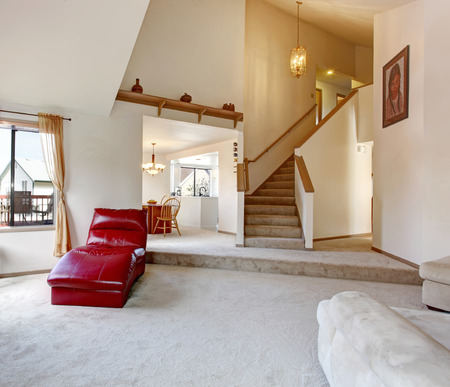 vaulted ceiling: High vaulted ceiling living room with hallway and stairs. Open to dining room and kitchen