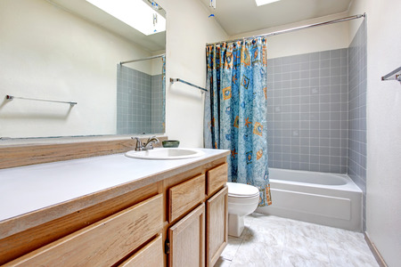 White bathroom with wood cabinets, tile floor. Refreshing blue curtains photo