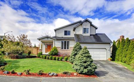 exteriores: Revestimiento casa con el garage y la columna del porche. Verde césped con setos recortados y crea el atractivo exterior se destacan Foto de archivo