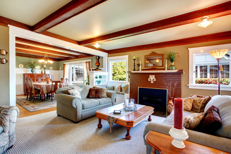 Big living room with grey carpet floor, ceiling beams, stoned fireplace.  photo