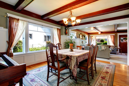 Beautiful dining room with olive and white walls, ceiling beams, hardwood floor and green rug. Furnished with antique dining table set and piano, decorated with palm pot. photo