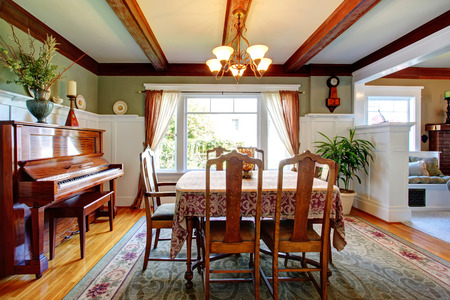 Beautiful dining room with olive and white walls, ceiling beams, hardwood floor and green rug. Furnished with antique dining table set and piano, decorated with palm pot and dry branches photo