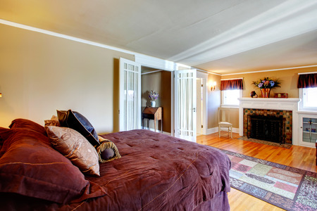 Bedroom with hardwood floor, rustic rug and fireplace. Decorated with beautiful flowers and cozy burgundy bedding.