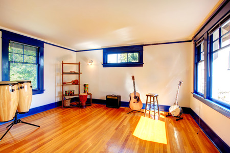 Bright room with blue window frames and hardwood floor. Rehearsal room with different instuments Stock Photo