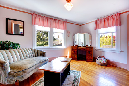 White and pink room with hardwood floor and rug. Furnished with coffee table, antique couch and wooden dresser cabinet with mirror. photo
