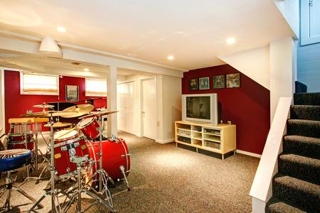赤とブルゴーニュの壁、カーペットの床と白い地下室。ドラムとリハーサル室