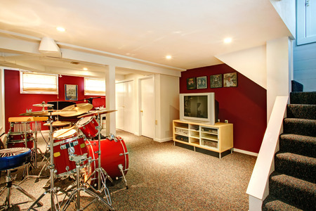 basement: White basement room with red and burgundy walls, carpet floor. Rehearsal room with drums Stock Photo