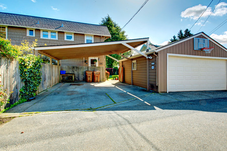 fenced: Fenced backyard with garage and attached cover, basketball court Stock Photo