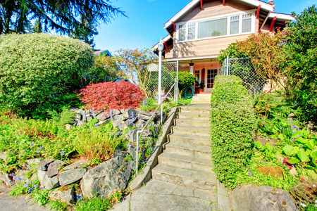 curb appeal: Two story house with  column porch and entrance gate. Beautiful stoned flower bed with green bushes and trimmed hedges. Stock Photo