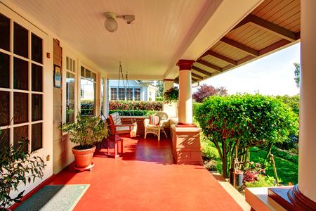 Grote veranda met kolommen, rieten rustieke stoel en opknoping schommel met uitzicht op voortuin met groene gazon en bomen Stockfoto