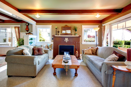 #25860670 - Big living room with grey carpet floor ceiling beams stoned background fireplace. Room furnished with sofa and loveseat rustic coffee table. & Big Living Room With Grey Carpet Floor Ceiling Beams Stoned ...