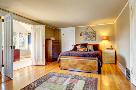 idea comfortable: Bedroom with hardwood floor rug. Furnished with antique dresser cabinet and carved wood bed. Room has a walkout bright office room Stock Photo