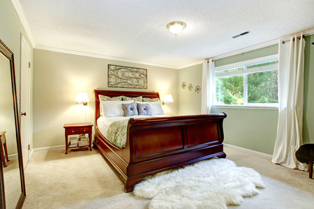nightstand: Bright bedroom with light mint wall, beige carpet floor, white soft rug. Furnished with cherry carved wood bed and nightstand