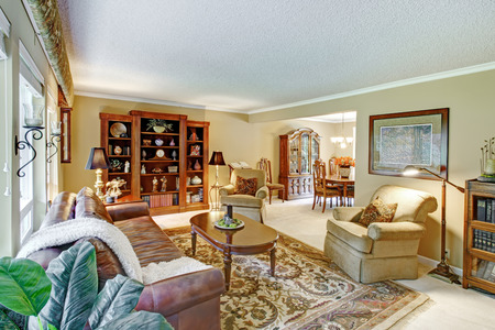 Brigh living room with carpet and rug, leather couch, chairs and wooden cabinet. Open to dining area photo
