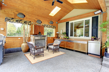 stoned: Backyard cabin style patio area with concrete floor and wooden cabinets, stoned fireplace and antique style chairs. Decorated with iron wall fishes, big vase with dry bamboo Stock Photo