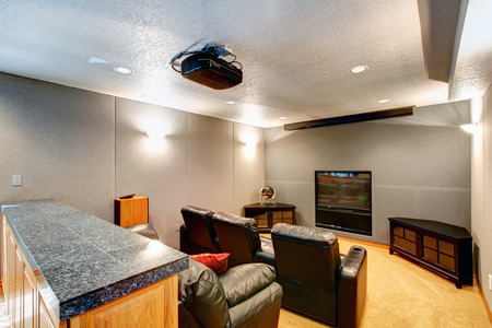 Big home theatre with black leather chairs and couch, black wooden cabinets, tv and projector.