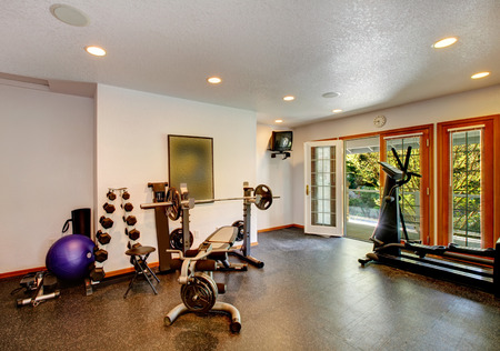 White and black home gym with different exercise equipments and tve Stock Photo