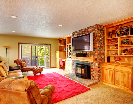 Comfortable living room with storage combination and brick wall together with fireplace and tv. Room furnished with antique armless leather chair, couch and loveseat, photo