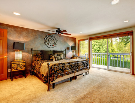 Big bedroom with walkout deck. Room furnished with antique iron frame bed, inlaid nightstand and decorated with iron wall art Stock Photo - 26069171