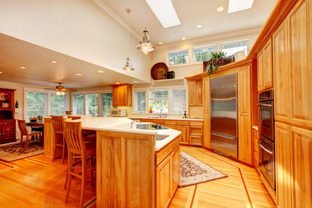 ceiling: Bright kitchen room with light brown storage combination and white counter tops, steel appliances, hardwood floor and rugs. High ceiling kitchen room estended to lower ceiling dining area.