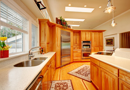 Bright kitchen room with light brown storage combination and white counter tops, steel appliances, hardwood floor and rugs
