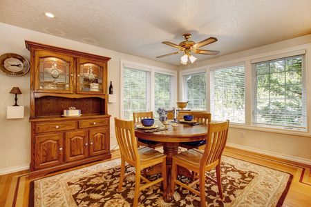 Bright dining room with rustic dining table set and wooden storage cabinet. Room has hardwood floor with soft brown and mocha rug