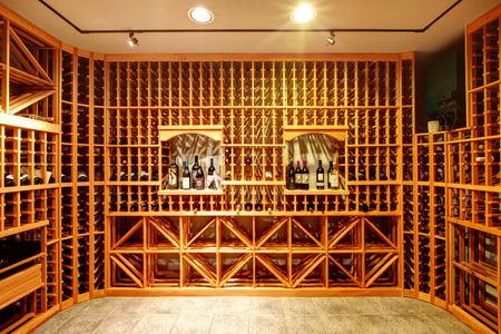 Lichte woning wijnkelder met houten kasten en boog met flessen.