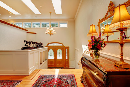 Fabulous high ceiling entrance hall and upstairs hallway with antique carved wood cabinet and wall niches. Decorated with beautiful flower bouquet and decorative horses photo