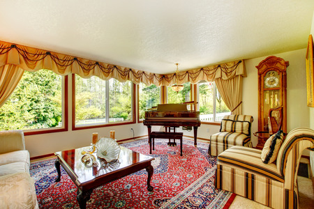 Bright living room with old fashioned couch and chairs, wooden coffee table, grand piano and antique oak grandfather clock